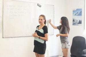 Etudiants qui font des exercices de français sur un tableau blanc